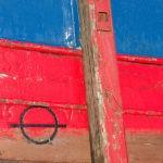 Photo, photographie de détail de coque de bateau du Finistère, bleu, rouge, marron, blanc, noir, avec une béquille @ Christophe Pluchon