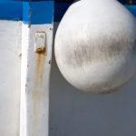 Photo, photographie de détail de coque de bateau du Finistère, bleu, rouge et blanc avec une béquille. Une grosse bouée pend au bout d'une corde ou d'un cordage @ Christophe Pluchon