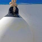 Photo, photographie de détail de coque de bateau du Finistère, bleu et blanc. Grosse bouée au bout d'une corde ou d'un cordage @ Christophe Pluchon