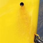 Photo, photographie de détail de coque de bateau du Finistère, jaune et rouge, avec du sable marron en arrière-plan @ Christophe Pluchon