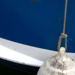 Photo, photographie de détail de coque de bateau du Finistère, bleu, noir et blanc avec une bouée couleur blanc et une corde ou cordage gris @ Christophe Pluchon