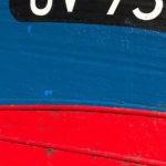Photo, photographie de détail de coque de bateau du Finistère, du quartier maritime du Guilvinec, rouge, noir et bleu @ Christophe Pluchon