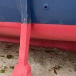 Photo, photographie de détail de coque de bateau du Finistère, rouge, bleu avec une béquille reposant sur le sable marron à côté d'algues vert et marron @ Christophe Pluchon