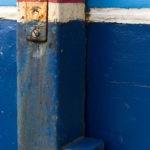 Photo, photographie de détail de coque de bateau du Finistère, bleu, blanc, rouge avec une béquille et un peu de rouille orange @ Christophe Pluchon