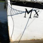 Photo, photographie de détail de coque de bateau du Finistère. Proue d'un voilier blanc et noir immatriculé dans le quartier maritime de Morlaix avec un filet et une bâche @ Christophe Pluchon