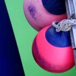 Photo, photographie de détail de coque de bateau du Finistère. Deux bouées rose et bleu d'un voilier sont retenues par une corde ou un cordage au-dessus de l'eau couleur vert @ Christophe Pluchon