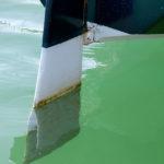 Photo, photographie de détail de coque de bateau du Finistère. Le gouvernail d'un voilier blanc et vert-bleu est dans l'eau couleur vert @ Christophe Pluchon