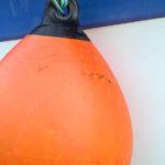 Photo, photographie de détail de coque de bateau du Finistère, bleu, vert, blanc, orange, noir, avec une grosse bouée et une corde ou un cordage @ Christophe Pluchon