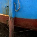 Photo, photographie de détail de coque de bateau du Finistère, bleu, rouge, marron, noir, rouille, orange, avec une béquille et une corde ou un cordage @ Christophe Pluchon