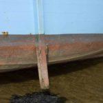 Photo, photographie de détail de coque de bateau du Finistère, bleu, jaune, rouge, marron, noir, rouille, orange, avec une béquille et du goémon sur le sable @ Christophe Pluchon