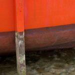 Photo, photographie de détail de coque de bateau du Finistère, orange, noir, marron, blanc, vert, avec une béquille sur le sable @ Christophe Pluchon