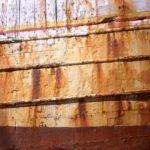 Photo, photographie de détail de coque de bateau du Finistère, rouge, jaune, marron, orange, rouille, blanc @ Christophe Pluchon