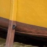 Photo, photographie de détail de coque de bateau du Finistère, orange, rouge, bordeaux, jaune, blanc, marron, avec une béquille @ Christophe Pluchon