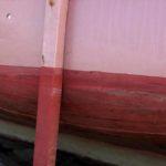 Photo, photographie de détail de coque de bateau du Finistère, rouge, rose, bordeaux, noir, marron, vert, avec une béquille @ Christophe Pluchon