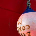 Photo, photographie de détail de coque de bateau du Finistère, rouge, blanc, bleu, orange, avec une corde ou un cordage et une bouée @ Christophe Pluchon