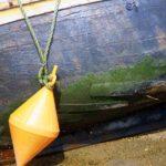 Photo, photographie de détail de coque de bateau du Finistère, jaune, bleu, vert, marron, blanc, avec une bouée sur le sable retenue par une corde ou un cordage @ Christophe Pluchon