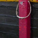 Photo, photographie de détail de coque de bateau du Finistère, rouge, noir, jaune, vert, avec une béquille, une corde ou un cordage @ Christophe Pluchon