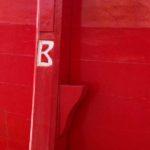 Photo, photographie de détail de coque de bateau du Finistère, rouge, vert, blanc, marron, bordeaux, avec une béquille @ Christophe Pluchon