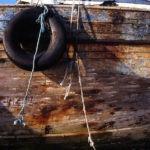 Photo, photographie de détail de coque de bateau du Finistère, marron, orange, bleu, noir, blanc, avec un pneu et une corde ou un cordage @ Christophe Pluchon