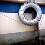 Photo, photographie de détail de coque de bateau du Finistère, bleu, blanc, gris, vert, rouge, marron, avec un pneu, une béquille et une corde ou un cordage @ Christophe Pluchon