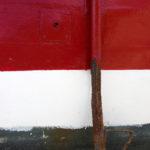 Photo, photographie de détail de coque de bateau du Finistère, rouge, noir, marron et blanc, avec une béquille et de la rouille @ Christophe Pluchon